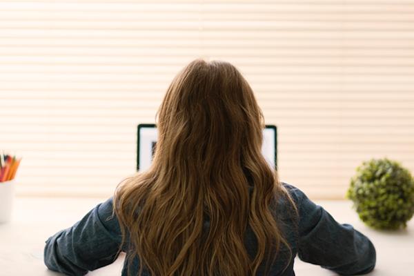 Woman facing her laptop